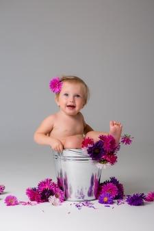 Menina sentada em um balde de flores