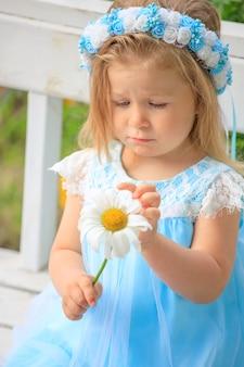 Menina sentada em um banco com um vestido azul e uma camomila