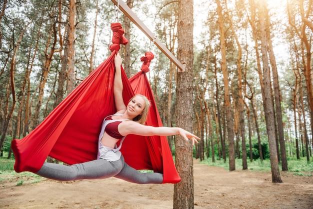 Menina sentada em um barbante numa rede para yoga.