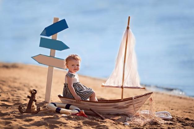 Menina sentada em um barco, vestida de marinheira na praia