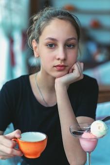 Menina sentada em um café com uma xícara na mão e sorvete na mesa.