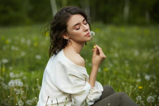 Menina sentada em um campo na grama primavera com flores-leão