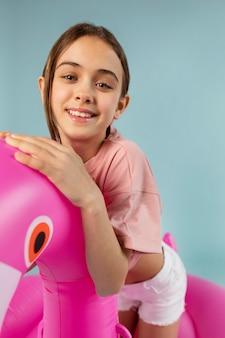 Menina sentada em um flamingo inflável tiro médio