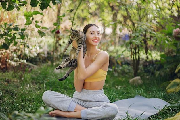 Menina sentada em um parque de verão com gato bonito