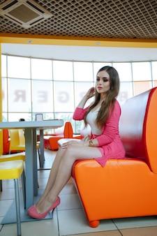 Menina sentada em um restaurante com um assento de laranja