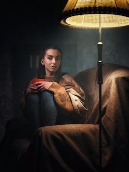 Menina sentada em uma cadeira à noite à luz da lâmpada