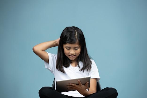 Menina sentada em uma cadeira assistindo tablet