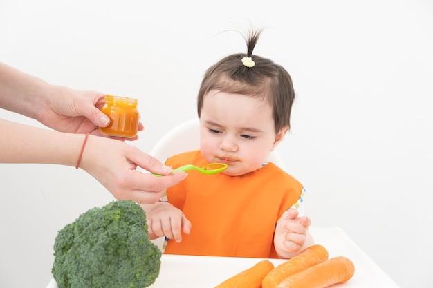 Menina sentada em uma cadeira de childs comendo purê de vegetais em fundo branco. mamãe alimenta o bebê.