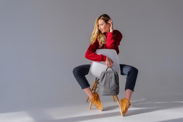Menina sentada em uma cadeira segurando uma mochila cinza