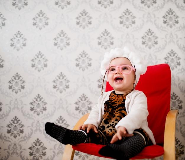 Menina sentada em uma cadeira. vestindo fantasia de vovó.