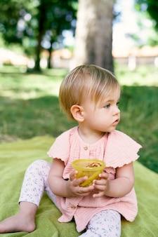 Menina sentada em uma colcha, virando a cabeça e segurando um pote