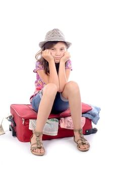 Menina sentada em uma mala