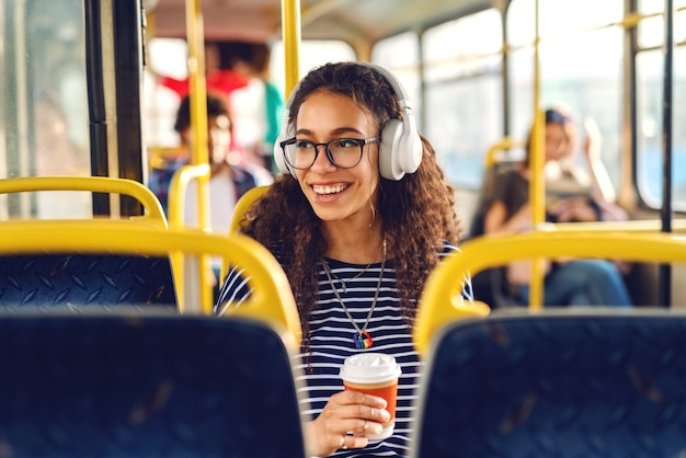 Menina sentada ina um ônibus tomando café, ouvindo música e olhando através da janela.