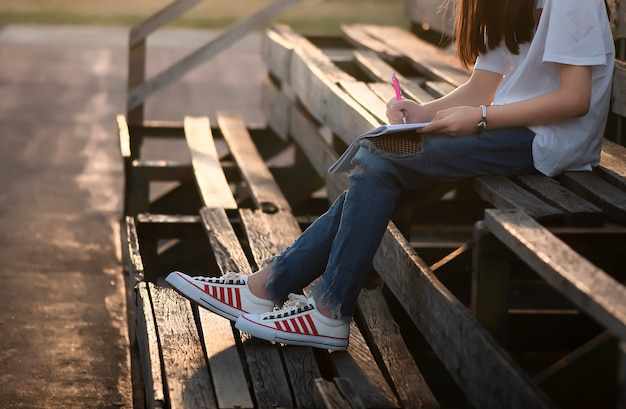 Menina sentada na bancada de madeira velha.