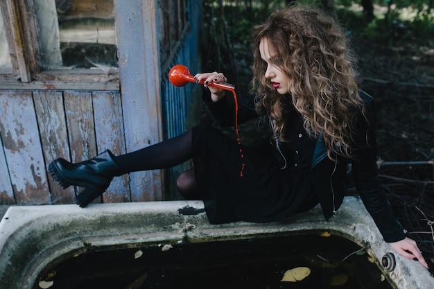 Menina sentada na beira de uma banheira com uma poção vermelha
