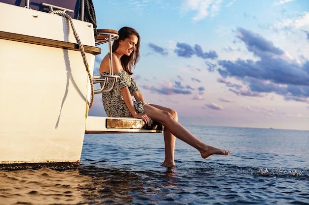 Menina sentada na beira do iate com as pernas espirrando água do mar