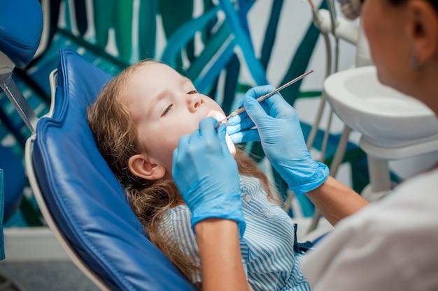 Menina sentada na cadeira do dentista
