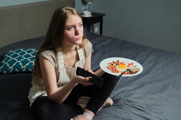 Menina sentada na cama com controle remoto, assistindo tv e comendo