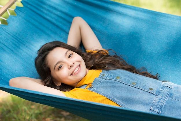 Menina sentada na cama de rede