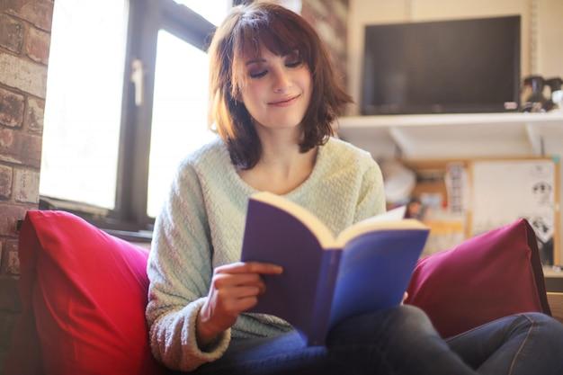 Menina sentada na cama, lendo um livro