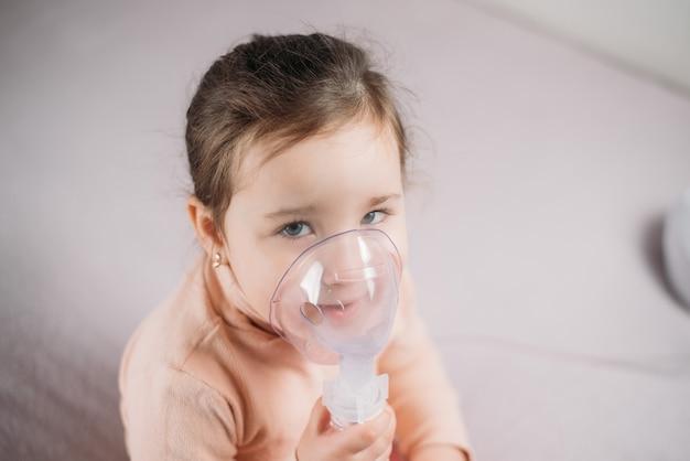 Menina sentada na cama no quarto com máscara de oxigênio