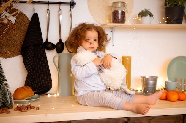 Menina sentada na cozinha de natal na mesa