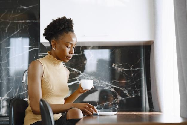 Menina sentada na cozinha. mulher bebendo café. senhora pela janela