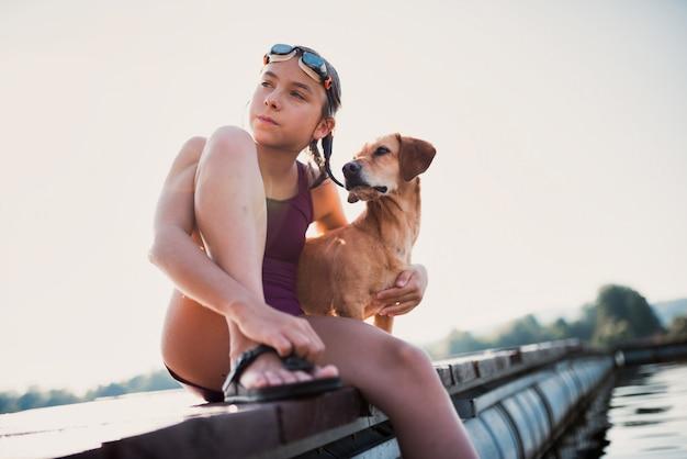 Menina sentada na doca do rio com seu cachorro