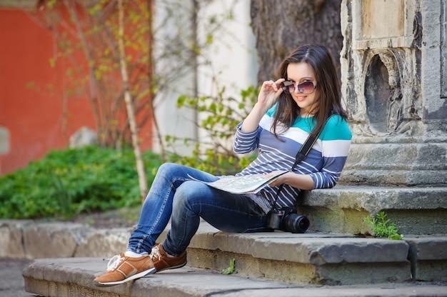 Menina sentada na escada com uma câmera e um mapa na mão
