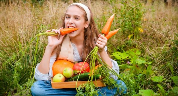 Menina sentada na grama comendo cenouras frescas, maçãs frescas, pepinos e abóbora em uma cesta