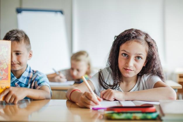Menina sentada na mesa de escrita