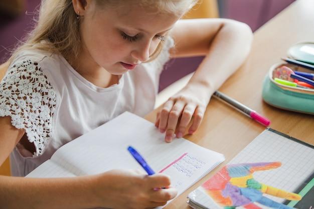 Menina sentada na mesa de escrita Foto gratuita