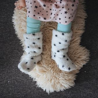 Menina sentada na pele de cordeiro no chão