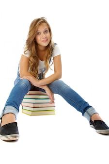 Menina sentada na pilha de livros