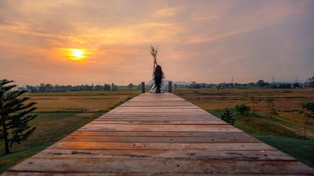 Menina sentada na ponte de madeira e aprecia o pôr do sol na natureza relaxe a vista à noite e vidro de flores, segurando a mão