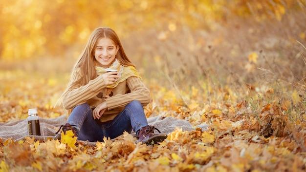 Menina sentada nas folhas amarelas