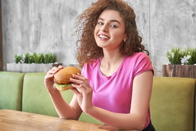 Menina sentada no café, segurando o saboroso hambúrguer, sorrindo.