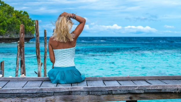 Menina sentada no cais de madeira de uma casa de família olhando para o oceano azul, ilha gam, papuã ocidental, raja ampat, indonésia