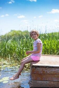 Menina sentada no cais do rio molhando os pés descalços na água