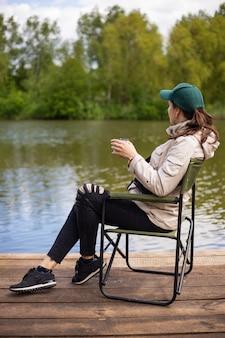 Menina sentada no cais, pescando no lago, sorrindo, vista traseira. atividades ao ar livre, lindo dia de verão.