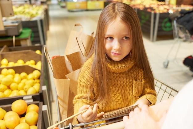 Menina sentada no carrinho de compras