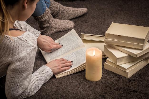 Menina sentada no chão cercada por muitos livros brancos e uma grande vela
