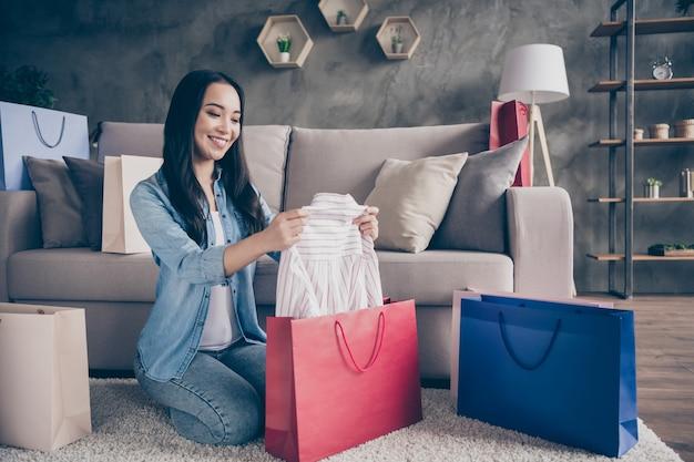 Menina sentada no chão com sacolas de compras