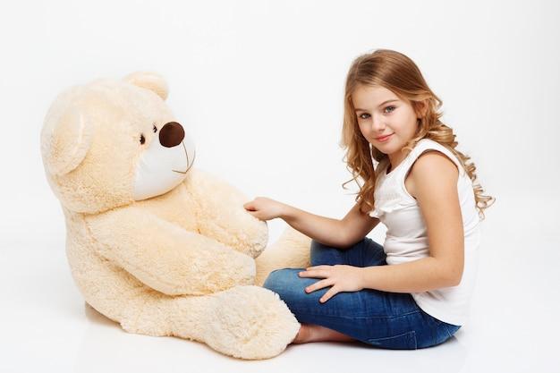 Menina sentada no chão com urso de brinquedo, segurando sua pata.