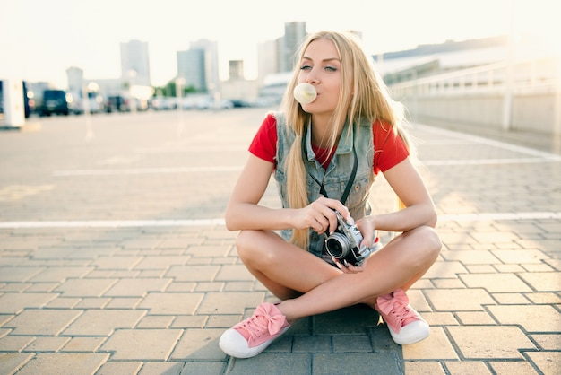 Menina sentada no chão e soprando bolhas de goma de mascar