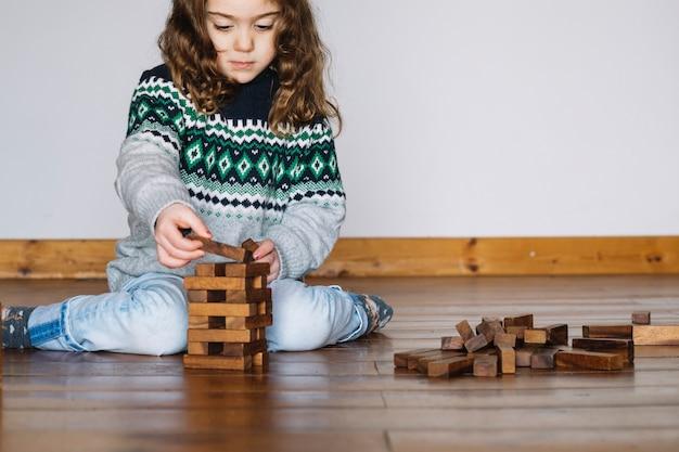 Menina sentada no chão, jogando jogo de jenga