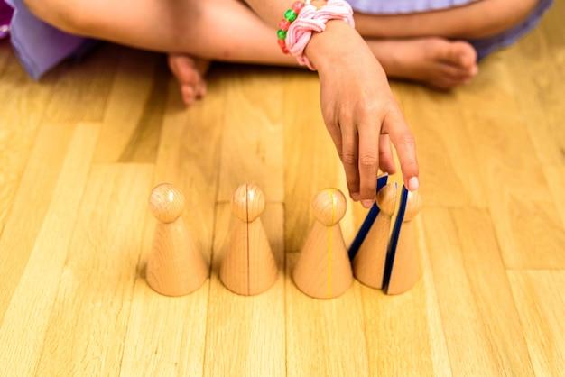 Menina sentada no chão na frente de um conjunto de material montessori para aprender frações.