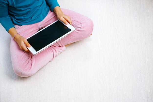 Menina sentada no chão olhando para o tablet com calças rosa e camisa azul