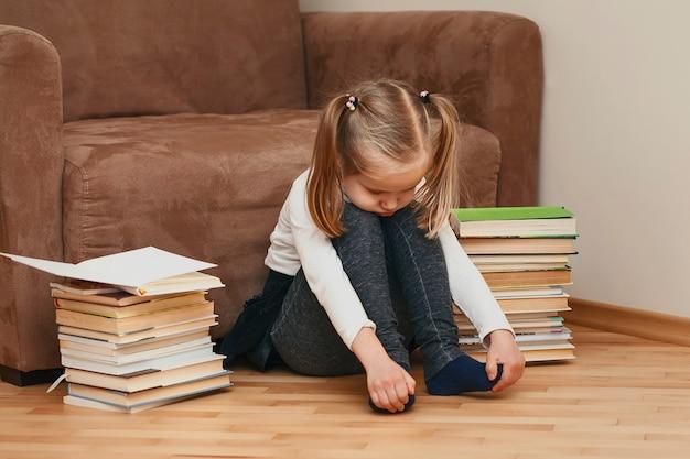Menina sentada no chão perto da cadeira e triste