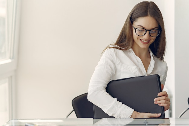 Menina sentada no escritório com um laptop